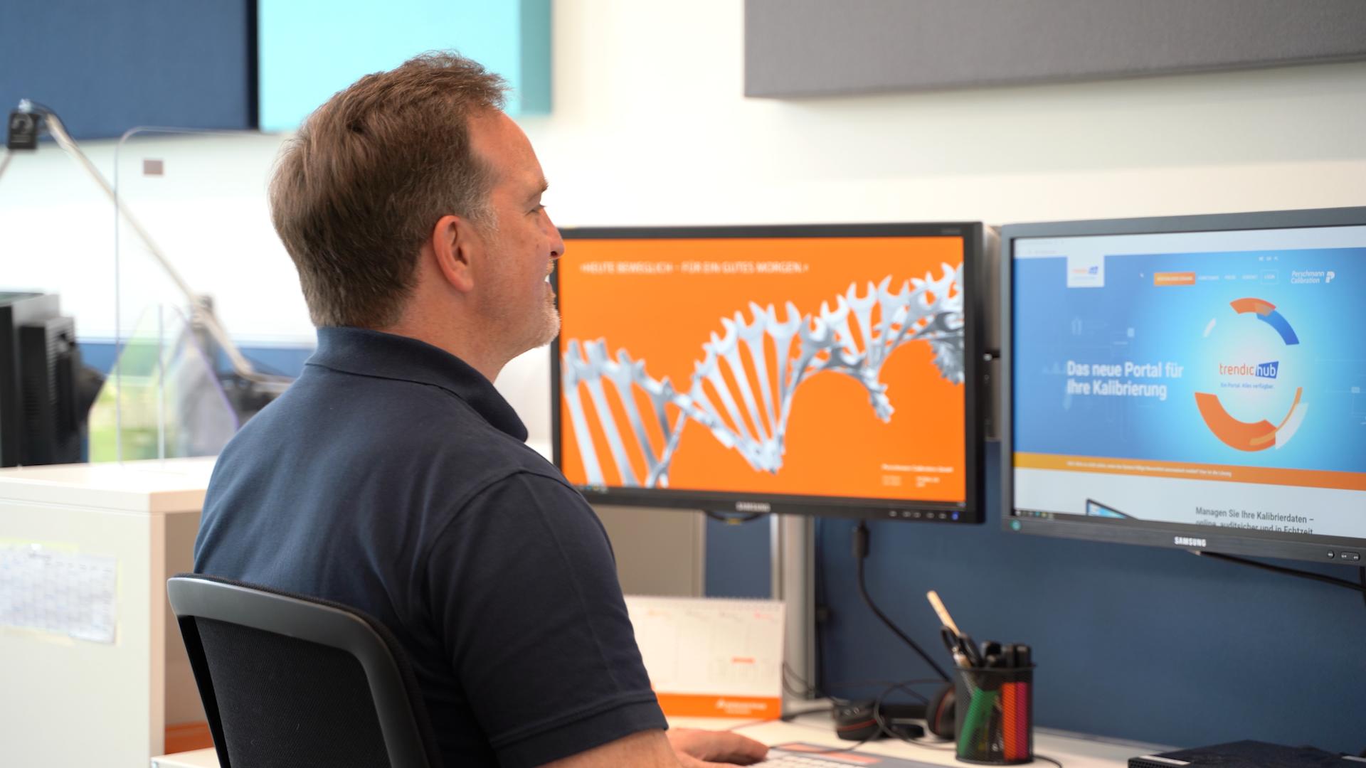 Ein Mann arbeitet an einem Monitor, auf dem die Startseite von trendic hub zu sehen ist
